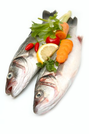 Fresh  Sea Bass (Dicentrarchus labrax) with some vegetables isolated on White Background photo