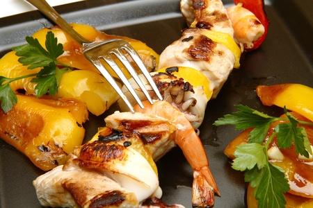 prepared fish kebabs with grilled pepper photo