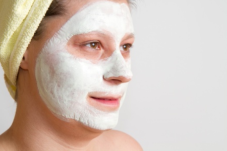 Portrait of a beautiful young girl wearing facial mud mask photo