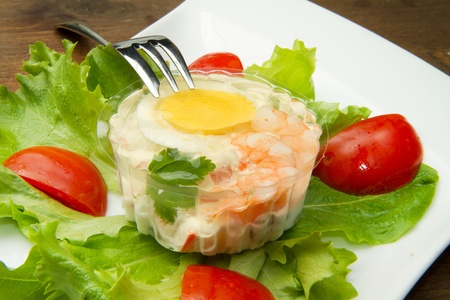 aspic with shrimps and eggs on fresh salad photo