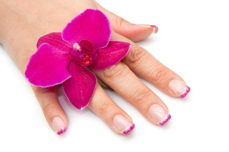 Beautiful hand with perfect nail french manicure and purple orchid flowers