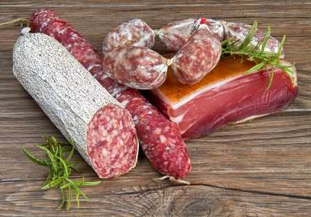 cured: A composition of different sorts of cold cuts on wooden table Stock Photo