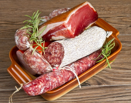 A composition of different sorts of cold cuts on wooden table photo