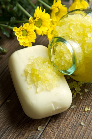Soap and yellow flowers on wooden table Stock Photo