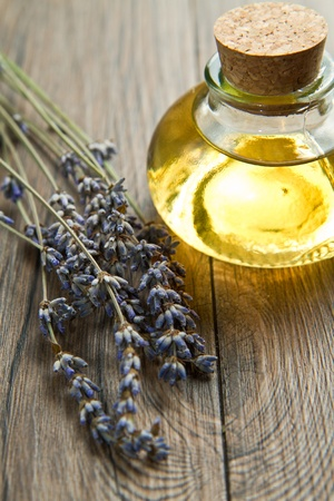 lavander oil with flowers on wooden table photo