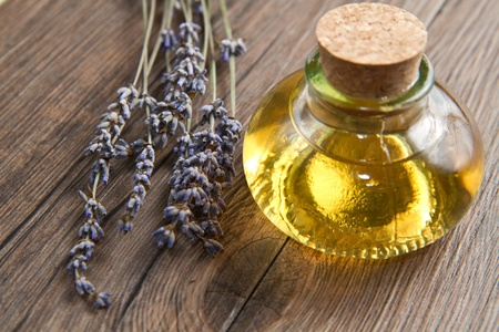 natural cosmetics: lavander oil with flowers on wooden table