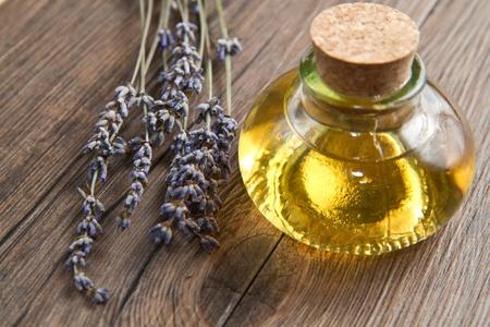 olio corpo: olio di lavanda con fiori sul tavolo in legno