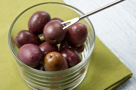 A small bowl of olives on a table  on wooden table photo