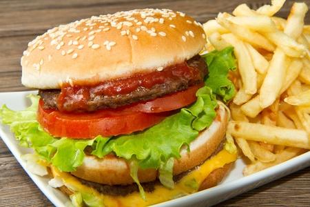 Hamburger avec pommes de terre sur fond en bois Banque d'images
