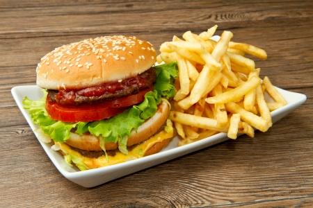 hamburguesa con patatas sobre fondo de madera
