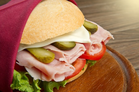 ham sandwich: sandwiches with ham and vegetables on wooden board