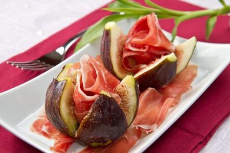 comida gourment: Higos frescos con jam�n en un plato blanco