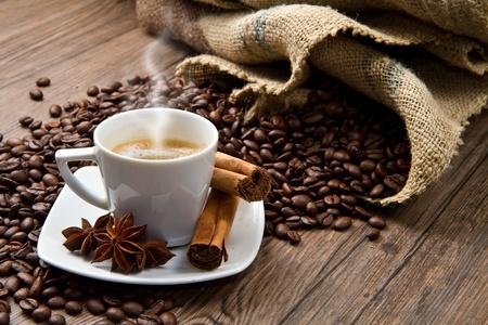 grano de cafe: Copa del caf� con saco de arpillera de frijoles asados en r�stica mesa  Foto de archivo