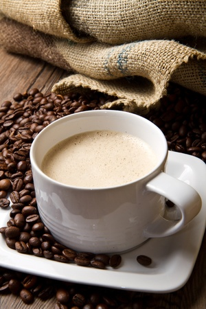 Coffee cup avec sac de toile de jute de torr�fi�s sur table rustique  Banque d'images