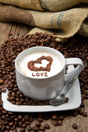 Coffee cup with burlap sack of roasted beans on rustic table Stock Photo - 10442923