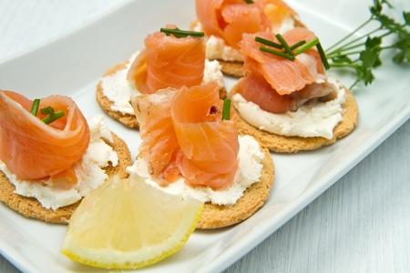 salmon ahumado: Canapé con salmón en plato blanco