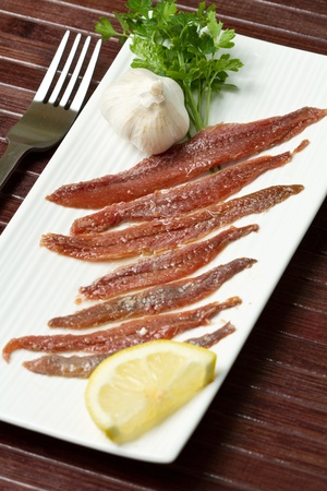 anchovy fish: fillet of anchovies with some ingredients on white dish Stock Photo