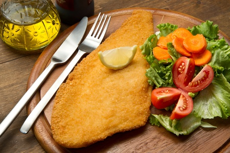 breaded: fillet of fried fish with fresh salad