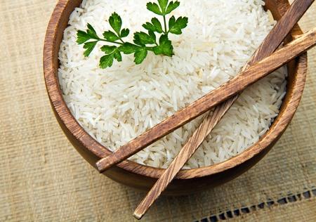 arroz blanco: granos de arroz crudo en un taz�n de madera