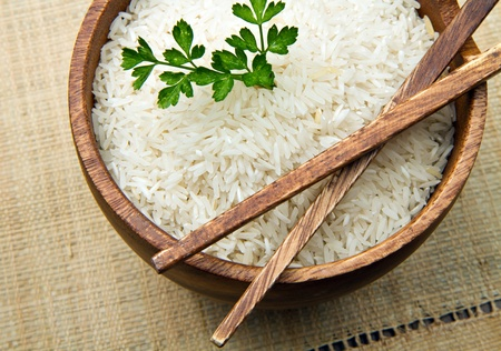 arroz chino: granos de arroz crudo en un tazón de madera