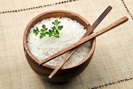 macrobiotic: uncooked rice grains in wood bowl