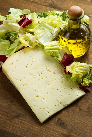 scamorza cheese: Asiago cheese with fresh salad on wooden table