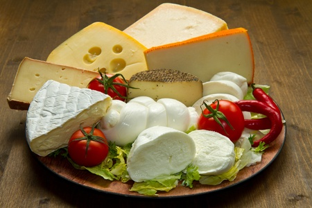 Various types of cheese on wooden board