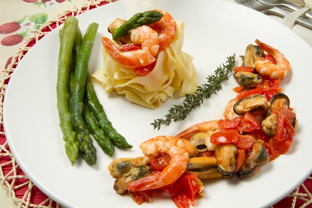 pasta with shrimp, mussels and fresh asparagus photo
