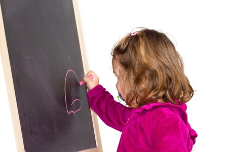 child draws with chalk on the blackboard  photo