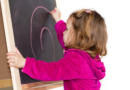 child draws with chalk on the blackboard Stock Photo - 12039884