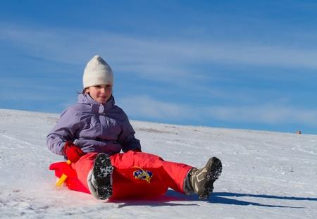 sledding: A girl sliding in the snow