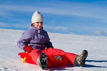 A girl sliding in the snow photo