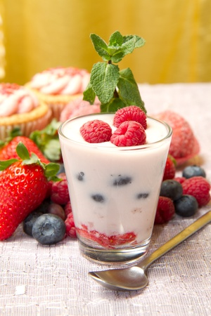 Yogurt with berries and cupcake Stock Photo