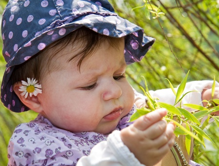 baby playing with blade of grass photo