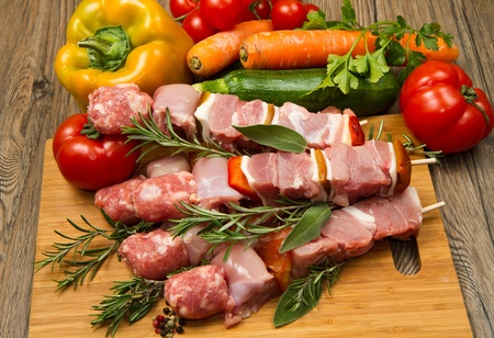 Meat and pepper skewers on a wooden cutting board  photo