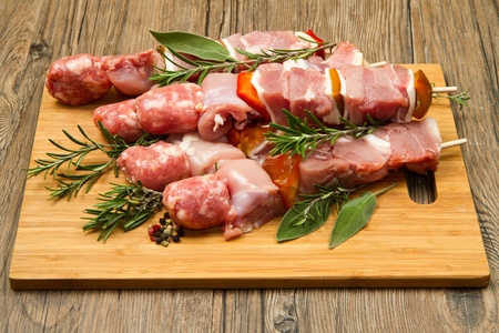 veal sausage: Meat and pepper skewers on a wooden cutting board Stock Photo