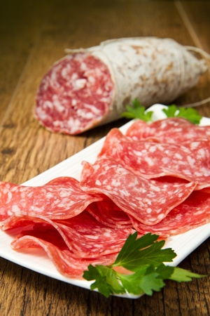 Salami sliced on wood background photo