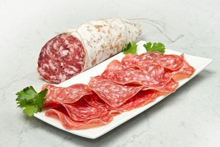 salami: Salami en rodajas sobre la mesa de mármol Foto de archivo
