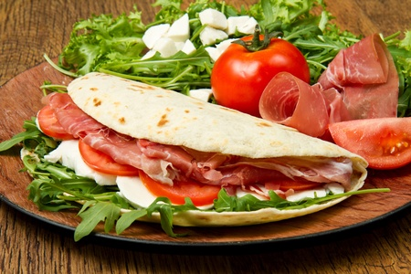 italian piadina with ham, fresh salad and mozzarella cheese Stock Photo - 13361614