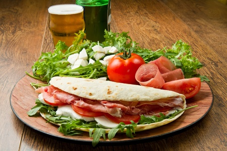 italian piadina with ham, fresh salad and mozzarella cheese photo