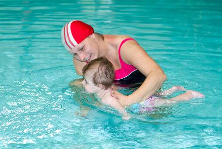 niños nadando: Joven de la familia con la diversión bebé que tiene en la piscina Editorial