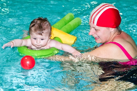 Young family with baby having fun in the swimming pool Stock Photo - 13413580