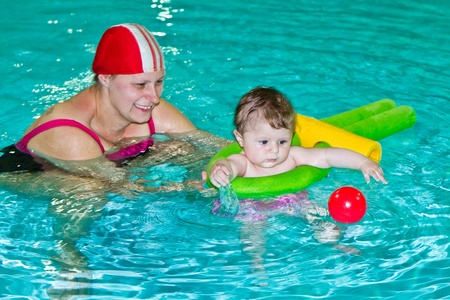 family with baby having fun in the swimming pool