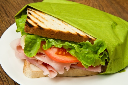 big sandwich with ham, cheese, tomatoes and salad on toasted bread  photo