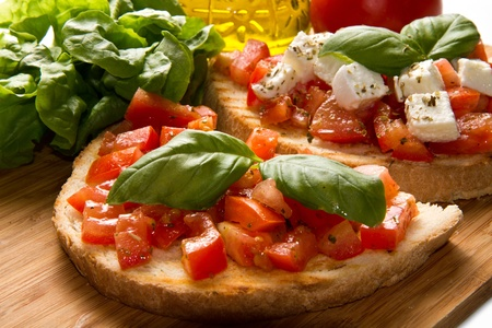 italian bruschetta with fresh tomatoes, basil, garlic, olive oil and cheese photo