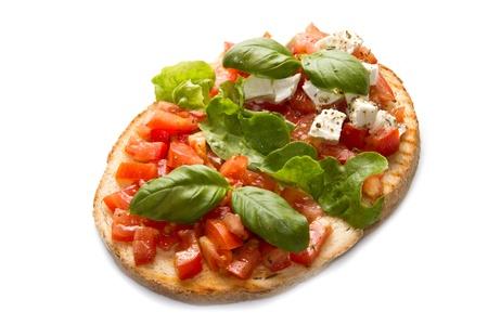 italian bruschetta with fresh tomatoes, basil, garlic, olive oil and cheese photo