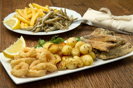 a dish with sardines fried and potatoes photo
