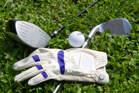 Collection of golf equipment resting on green grass  photo
