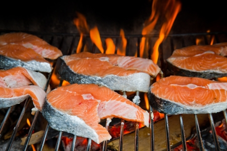 grilled fish: a fresh steak of salmon on grilled with flames