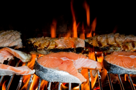 a fresh steak of salmon on grilled with flames photo